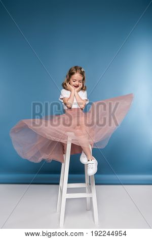 Adorable Little Girl In Pink Skirt Sitting On Ladder And Looking Down