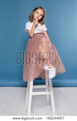 Cute Pensive Little Girl Sitting On Ladder And Looking Away