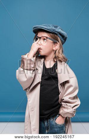 Adorable Little Girl In Cap Adjusting Eyeglasses And Looking Away