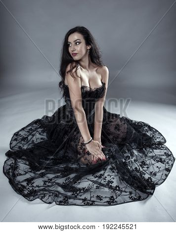 Young woman in black lace dress on gray background