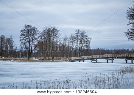 A Beautiful Winter Landscape With A Bridge Over The Frozen River