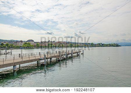 Zurich Switzerland - June 10 2017: Shipping pier at Burkliplatz where excursion boats starts over Lake Zuerich. Opera of Zurich in the background - eastern shore.