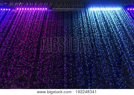 curtain of falling water with colorful led light on dark background selective focus