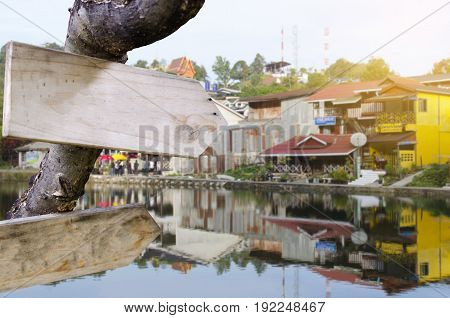 empty blank wooden signs or billboard for text with view of blurred beautiful village near lake with mirror reflection in water from thailand selective focus copy space sunlight effect