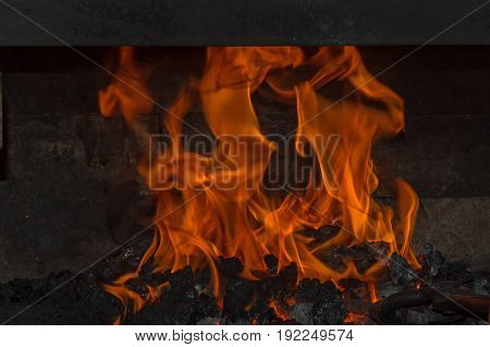 Orange flames blaze and dance brightly inside the coal forge