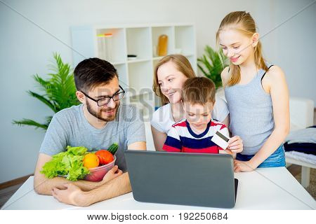 Happy family shopping online with a credit card