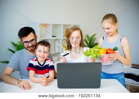 Happy family buying food online with laptop