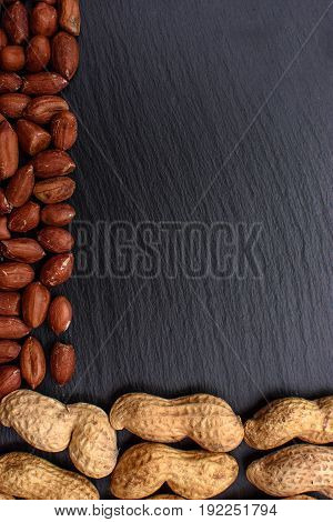 Untreated Peanuts And Peeled On A Black Stone Board, Space For Text