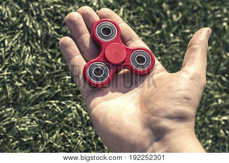 Cool red fidget spinner lies on the palm of the hand caucasian man on green artificial field background. Popular spinner gadget in 2017.