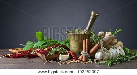 Different Herbs And Spices On A Wooden Table .