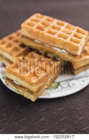 Sweet Viennese waffles with white filling lie on a saucer on a dark brown background vertical frame