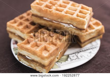 Delicious Viennese waffles with a filling lie on a saucer on a dark brown background close-up