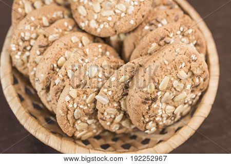 A delicious homemade cookie with cereals and seeds lies in a wicker basket on a saturated brown background