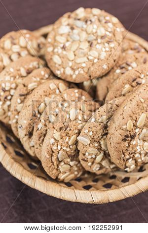 Homemade fitness cookies with cereals and sunflower seeds lies in a wicker basket on a dark brown background a vertical frame
