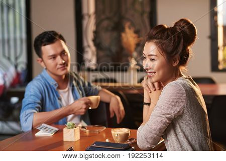 Portrait of beautiful Asian woman enjoying evening in cafe with man watching her in background