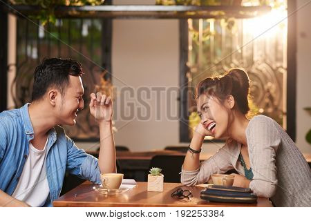 Side view portrait of laughing Asian couple enjoying date in cafe