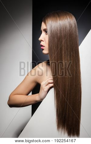 Half face of attractive young brunette with long shining hair