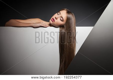 Sensual young woman with eyes closed and shining brunette hair