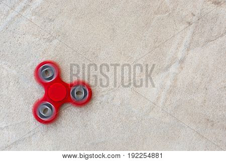 d fidget spinner in motion stress relieving toy on concrete background.