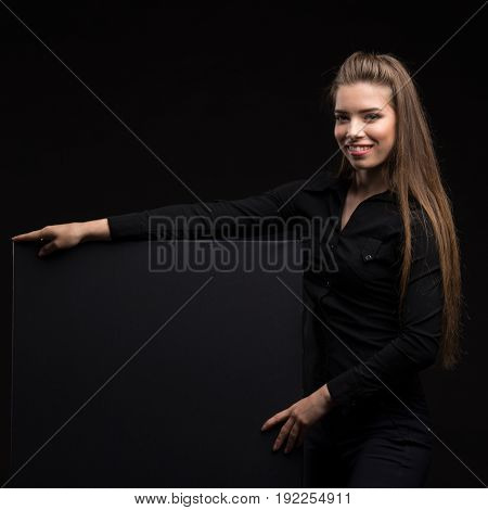 Young happy woman portrait of a confident businesswoman showing presentation, pointing placard gray background. Ideal for banners, registration forms, presentation, landings, presenting concept..