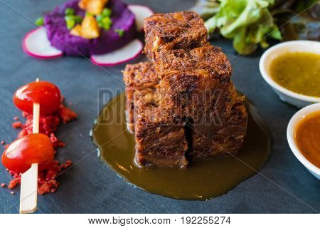 Close up square deep fried crispy pork knuckle cube with spicy sauce and tomato Thai French fusion style