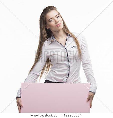Young sexy woman portrait of a confident businesswoman showing presentation, pointing placard gray background. Ideal for banners, registration forms, presentation, landings, presenting concept..