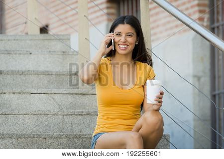 attractive latin woman in her twenties happy talking her mobile smart phone while drinking a coffee sitting on stairs.