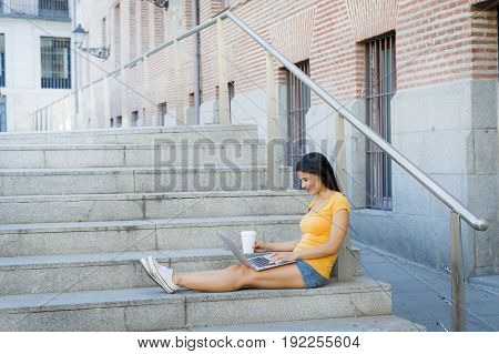 attractive latin woman in her twenties happy and working on her laptop outside in europe.