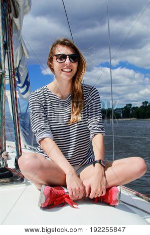 Pretty woman sits on a yacht and smiles against the blue sky