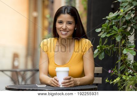 Attractive Latin Woman Sitting Drinking Coffee