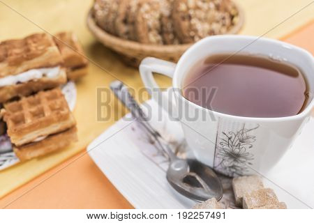 White with a floral pattern mug with tea a spoon and lump brown sugar lie on a white square saucer next to the defocus of Viennese waffles and cookies on a warm pear-yellow and light orange background.
