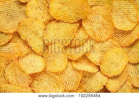 Yellow salted potato chips as background. Chips texture studio photo