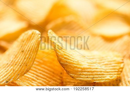Yellow salted potato chips as background closeup. Chips texture studio photo