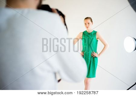 Male photographer working with female model in studio
