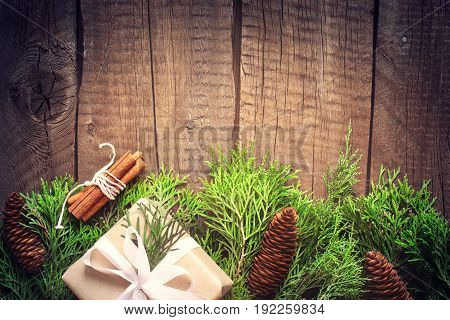 Coniferous branches with cones on old wooden boards. Natural Christmas New Year background. Toned