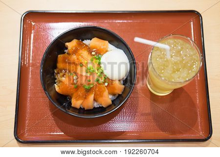 Set of rice bowl with salmon sashimi and onsen egg decorated with vegetable in japanese restaurant.