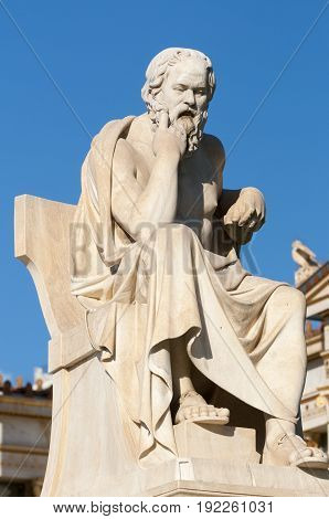 classical statue of Socrates sitting, under blue sky
