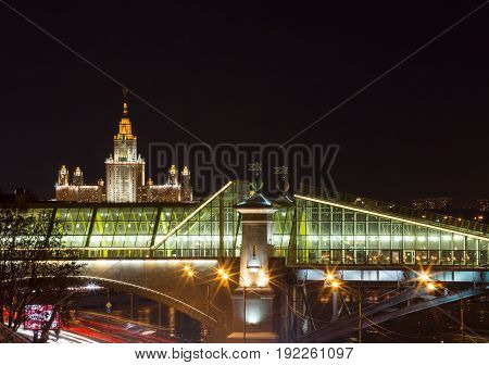 Lomonosov Moscow State University at cloudless winter night in the foreground a pedestrian bridge Bogdan Khmelnitsky across the Moskva River the bright colorful lights.