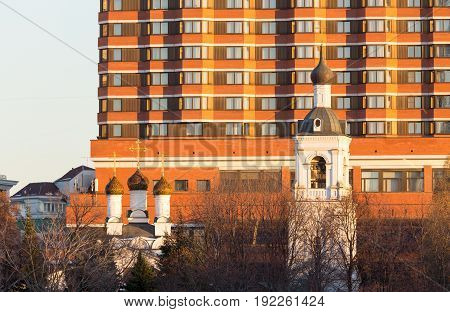 Orthodox church and bell tower on the background of the hotel in central Moscow at the sunset on sunny winter day in Moscow Russia