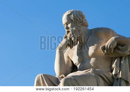 classical statue of Socrates from side, under blue sky