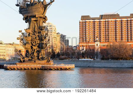 Moscow Russia - November 22, 2016: the lower part of the Peter The Great statue on the Moskva River and orthodox church with bell tower on the background of the President-hotel in central Moscow at the sunset on sunny winter day in Moscow Russia