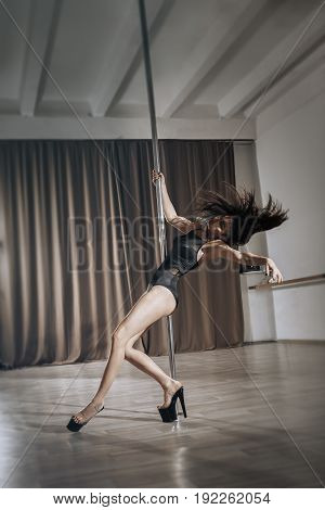 pole dance performing Beautiful woman Shot with industrial concrete background. The hair of a sexy girl flies in different directions.