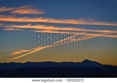Orange contrails on the sky during the sunset