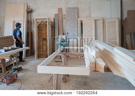 carpenter's place of work, Carpenter with tools and wood work pieces