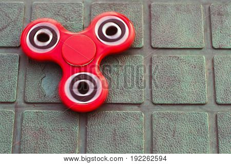 Top view of the popular red spinner gadget in 2017 on the blue-green background. Popular spinner gadget in 2017.