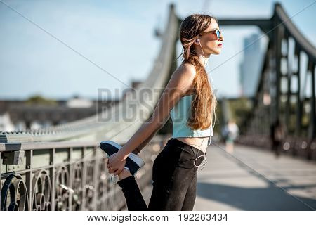 Young woman in sportswear having a morning exercise stretching on the iron bridge in Frankfurt city