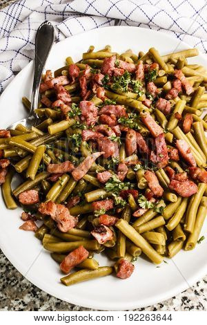 cooked green beans and roasted bacon bits on a white plate