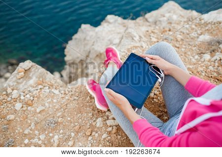 Woman in pink sneakers,a sports jacket pink,gray sweat pants and gray t-shirt,sitting in the open air, on the high rocky shore, against the blue of the ocean,ready to listen to music on your tablet through the white headphones