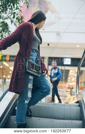 young woman on escalator in mall goes up