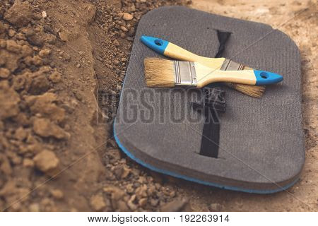 Archaeological tools (two brushes, mat) on a land separation on archaeological excavations